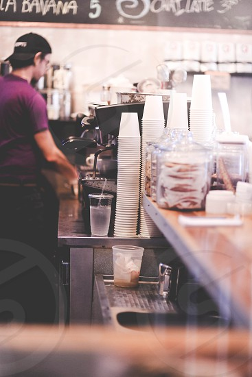 man in purple shirt standing beside black coffeemakers near white disposable cups on table photo