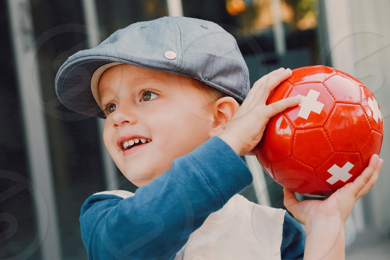 boy in gray fitted cap holding red ball photo