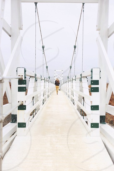 woman in black jacket and yellow pants running on white and green painted bridge photo