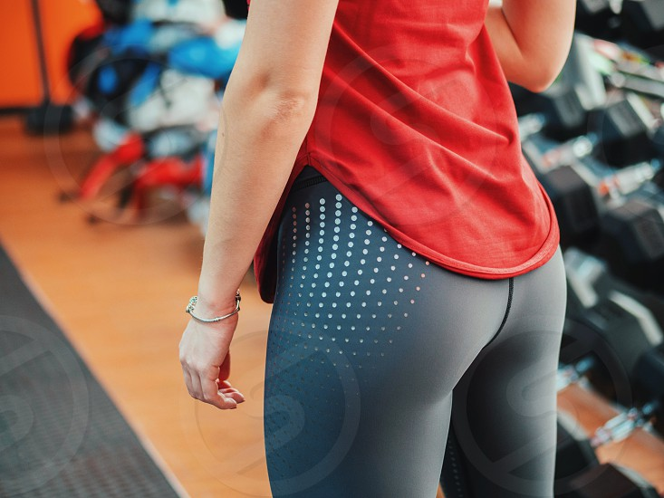 beautiful slender girl in sportswear in the gym. focus on the buttocks photo