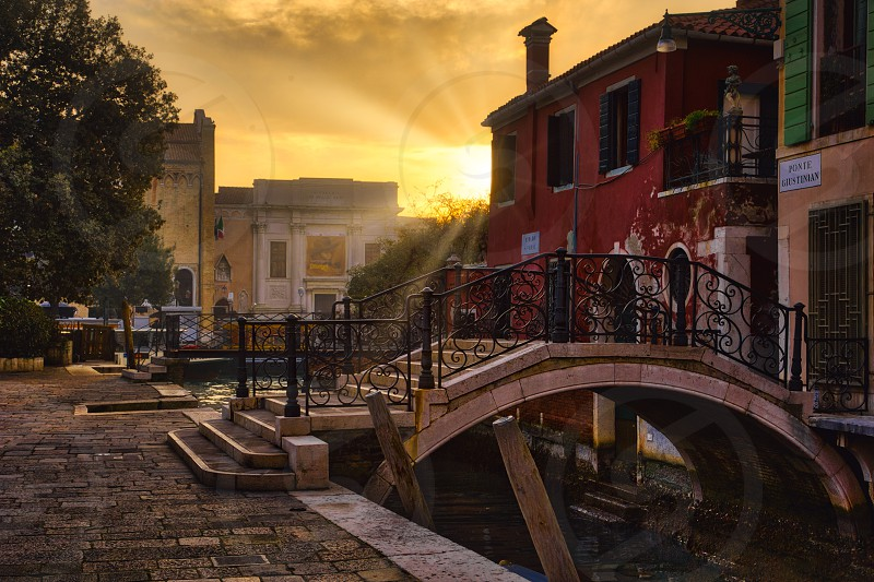 sunset on a small bridge in venice italy photo