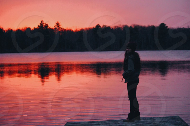 woman standing on the edge of brown wooden surface near body of water during sunset photo