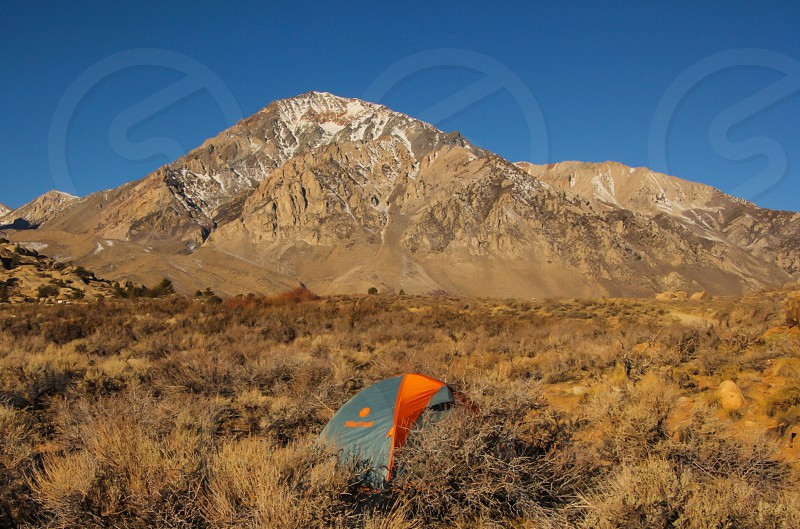 grey and orange tent in front of brown mountain photo