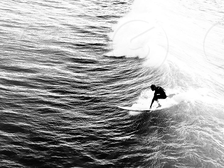grayscale photography of surfer riding water wave photo