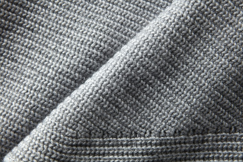 A full page close up of gray knitted jumper material texture photo
