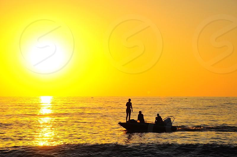 3 men in speedboat on ocean at sunrise photo