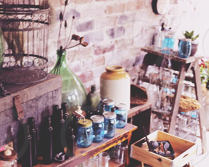 room with exposed brick wall glass bottles and mason jars on table  photo