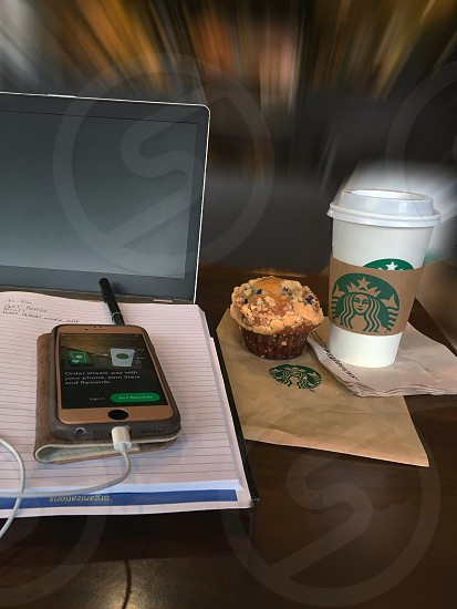 Mobile workspace in Starbucks coffee shop with blurred background showing beverage muffin notebook laptop computer cell phone and pen on table top photo