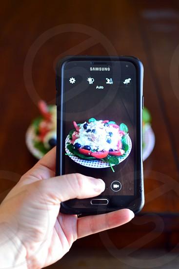 person taking picture through black samsung smartphone photo