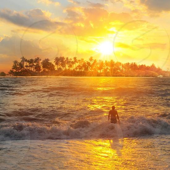 man on beach over sunrays photo