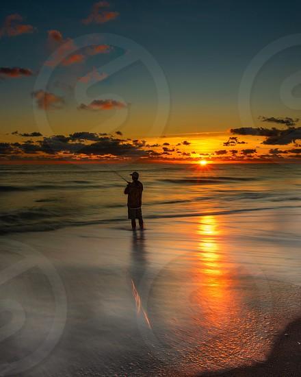 Sunset beach ocean fishing photo