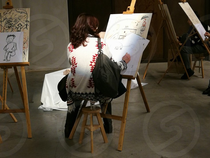 woman wearing white and red sweater with brown handbag sketches person photo