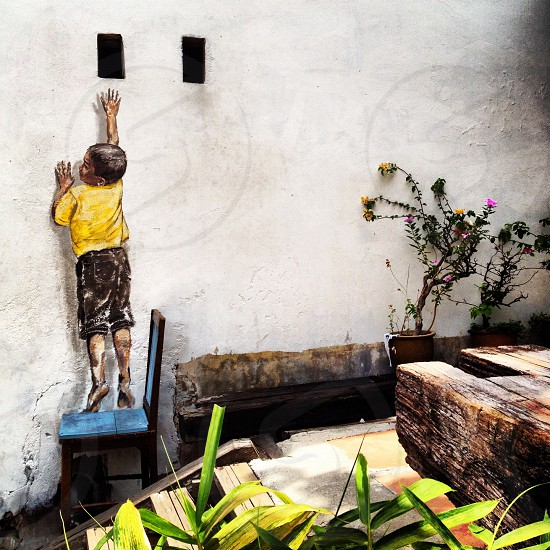 boy wearing yellow shirt standing on chair painting photo