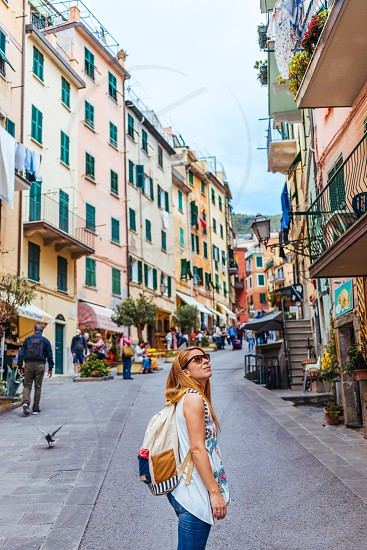 Beautiful young woman enjoying the view of Manarola in the UNESCO World Heritage Site Cinque Terre Liguria Italy photo