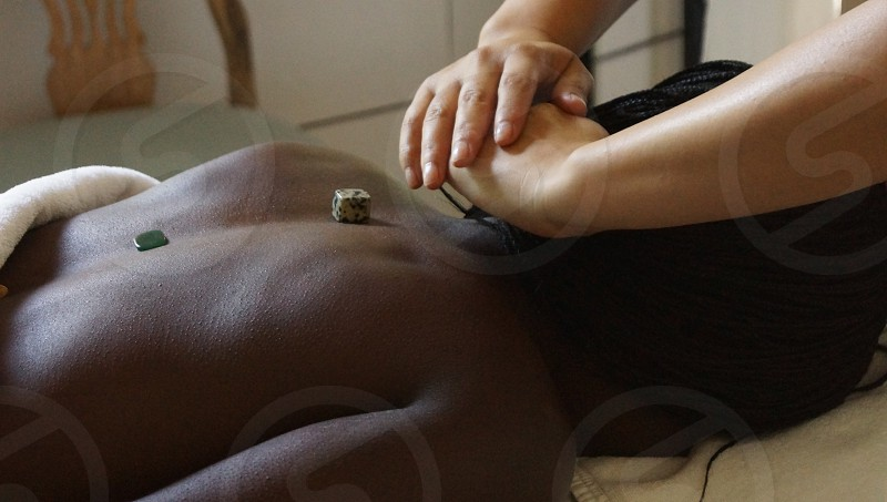 Black woman with braids laying on a massage table with nude back receiving a quartz-stone massage-therapy session by a white subject with only arms visible. photo