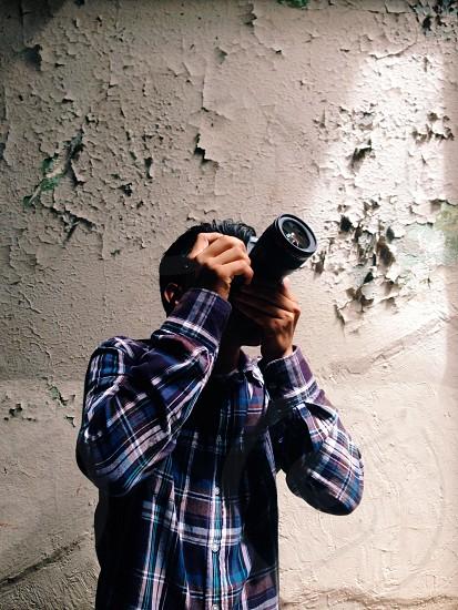 man in blue plaid button down shirt taking a photo photo