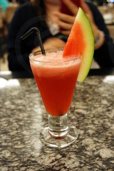 watermelon wedge on drinking glass with straw photo