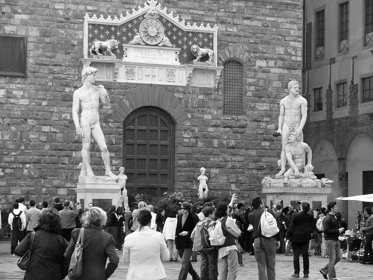 3 male statue and people walking photo