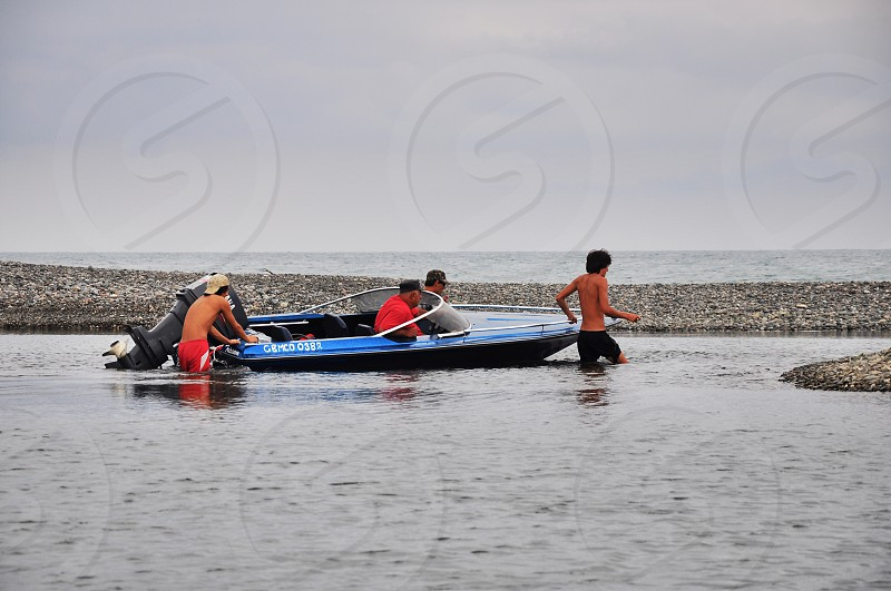 men riding inflatable motor boat photo