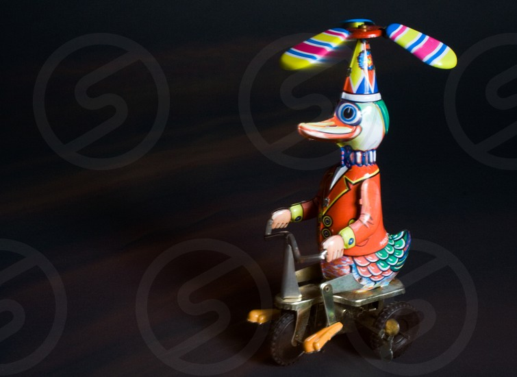 red and green duck riding bicycle plastic toy photo
