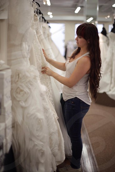 woman in tank top looking through wedding dress rack in store photo