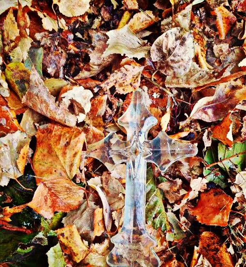 Clear colored cross resting on a bed of freshly fallen autumn leaves.  photo