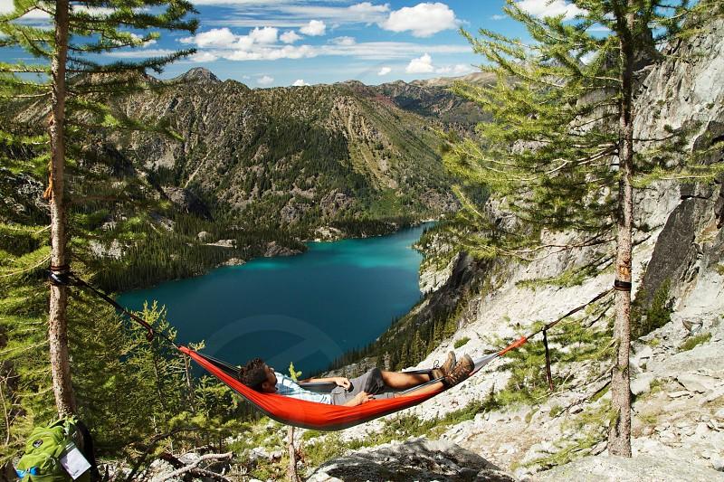 man sleeping inside orange hammock photo