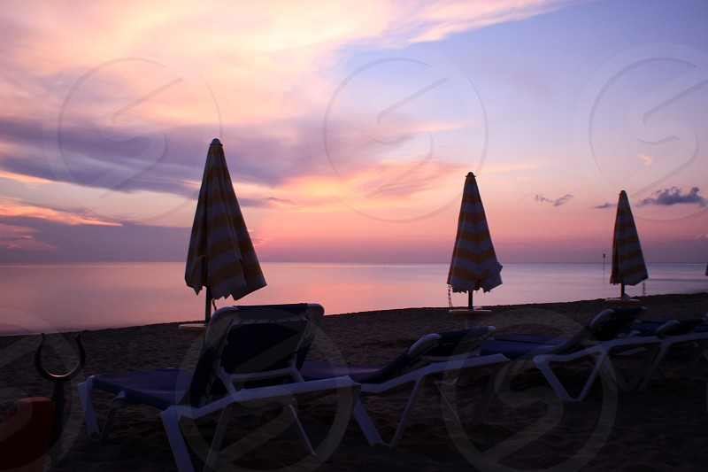 empty beach chaise lounge chairs and folded umbrellas by the beach during sunset photo
