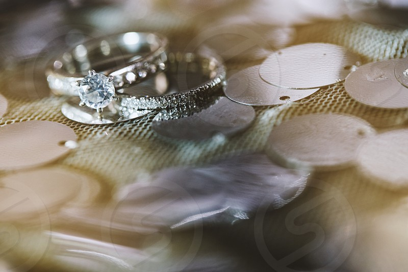 The close-up shot of the wedding engagement rings of the bride and groom focused on the diamond ring of the bride with glitter and shine with copy space photo