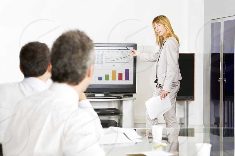 business; businesspeople; meeting; man; woman; presentation; teamwork; chart; office; indoors; side view; waist up; looking; sitting; standing; smiling; copy space; businessman; businesswoman; colleagues; working; meeting room; well-dressed; caucasian; technology; happy; communication; cooperation; Togetherness; conference table; ideas; using laptop; two people; young adult; mature men; 40s; 30s; partnership; business relationship; gray hair; blond hair; holding; pen photo