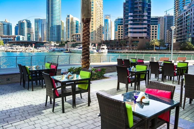 Cityscaperestaurant cafe open air seating colourful chairs chairs and tables buildings cafe by the sea cruises beach side Dubai Dubai JBR Dubai marina Jumeriah beach residence  photo