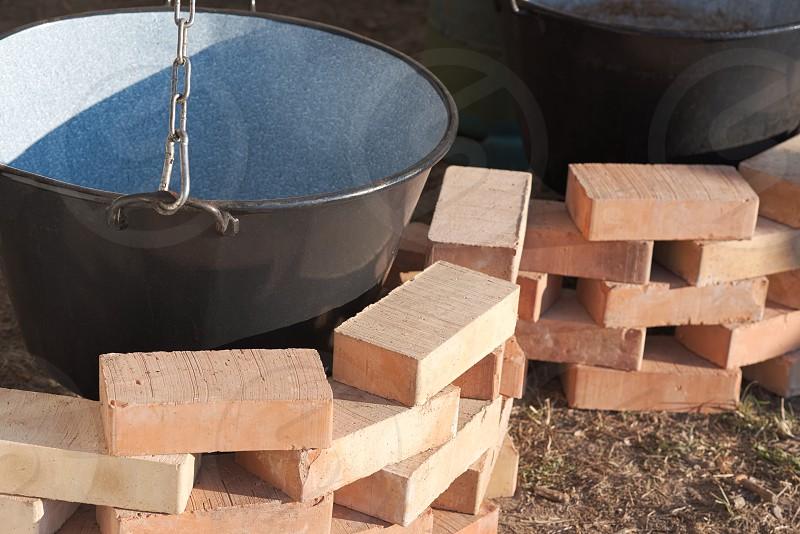 Empty Clean Black Cauldrons and New Bricks Closeup photo