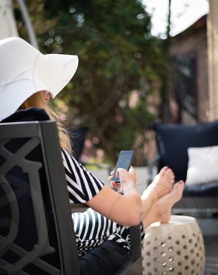 Relaxed woman with feet up browsing social media on smartphone photo