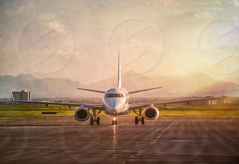 white airplane running on runway during sunrise photo