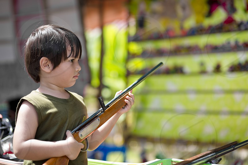 Kid holding a toy gun at the fun fair playing game shootingweapontargetaimconcentrationwintraintrainingarmy photo