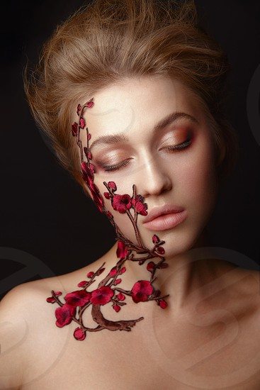 Studio Portrait of a young woman with flower makeup photo