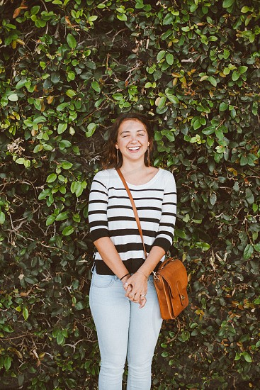 smiling woman in white and black striped quarter sleeve shirt with brown leather satchel bag standing in front of green vine plants on wall during daytime photo