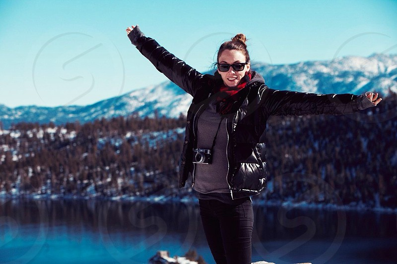 Woman wearing a black winter coat holding out her arms photo