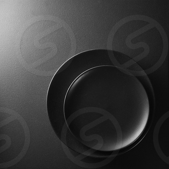 Black plates on a textured black background. photo