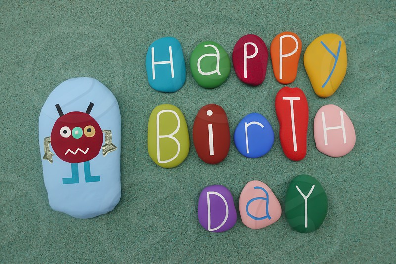 Creative Happy Birthday composition with colored stones design over green sand                                photo