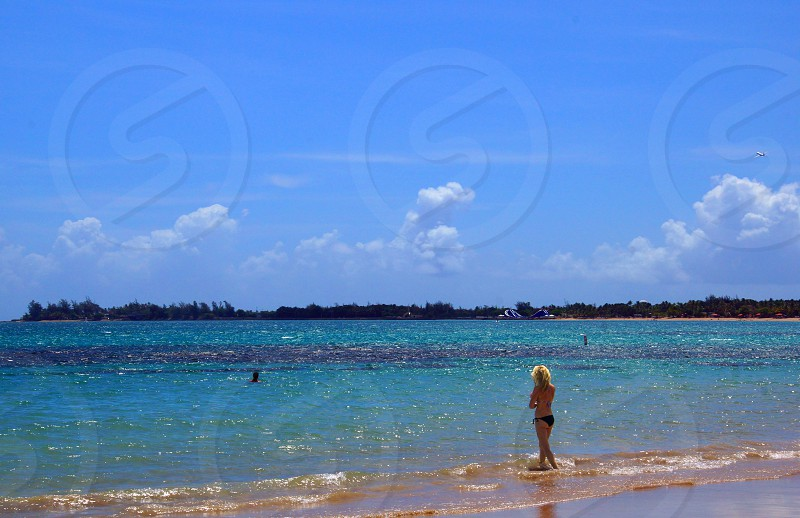 woman in black bikini standing on sea side under blue and cloudy sky photo