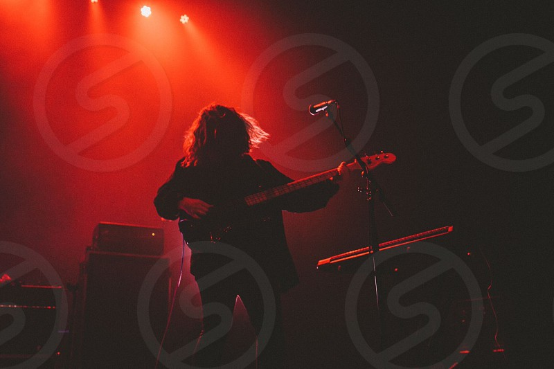 bass player performing on red lighted stage photo