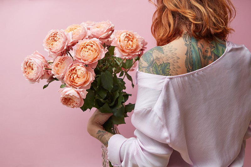 Girl with a tattoo on her back holds a big bouquet of pink roses media on a pink backgroundview from the back. Valentine's Day Mother's Day photo