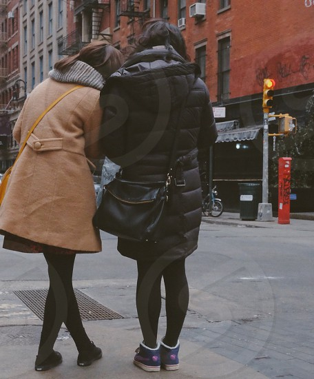 woman in black bubble trench coat with black leather sling bag standing near woman in brown trench coat on sidewalk during daytime photo