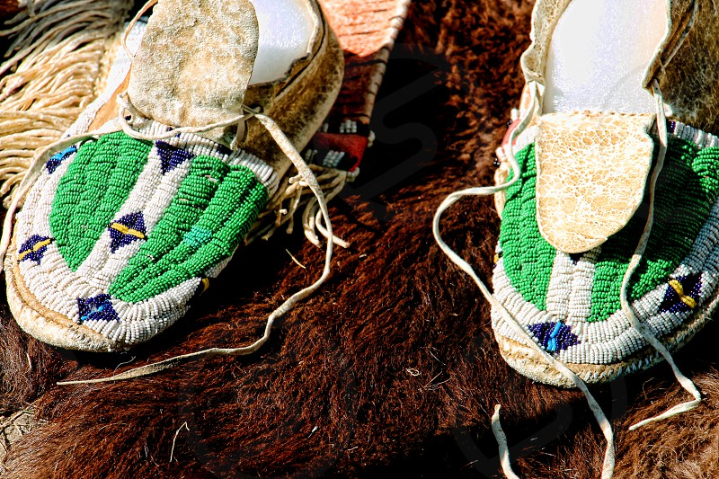 native American beaded moccasins on a fur hide. photo