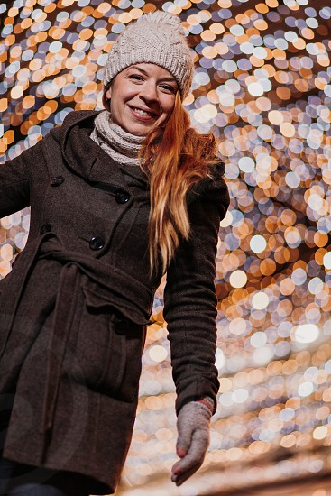 Young happy woman with Christmas light on the street photo