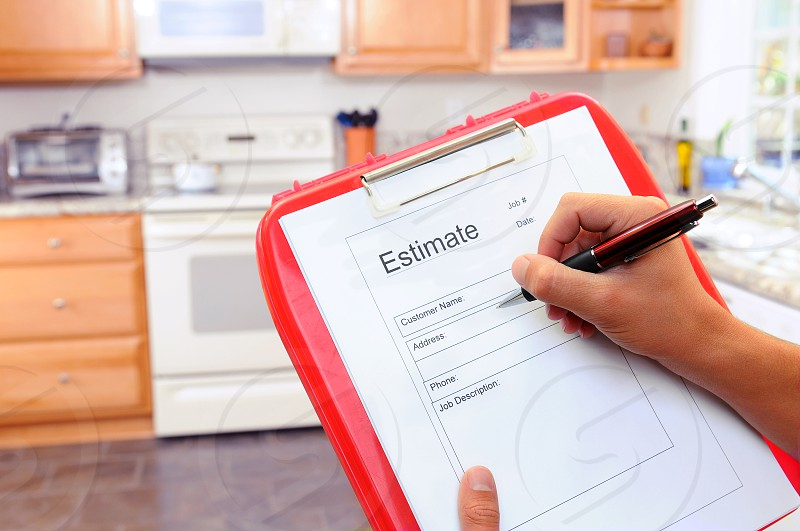 Closeup of a contractors clipboard as he writes up an estimate for a kitchen remodel. Shallow depth of field with focus on clipboard. photo