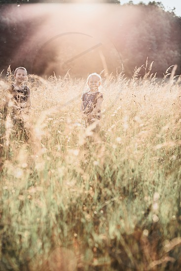 Little happy smiling kids playing in a tall grass in the countryside. Candid people real moments authentic situations photo