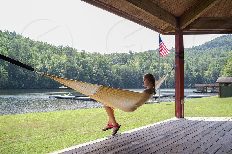 woman sitting on yellow hammock by green grass field photo