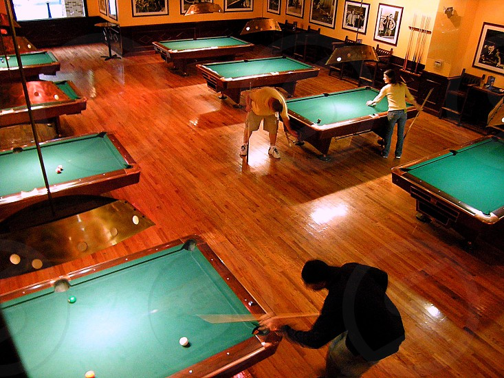 Three people playing pool in a pool hall photo